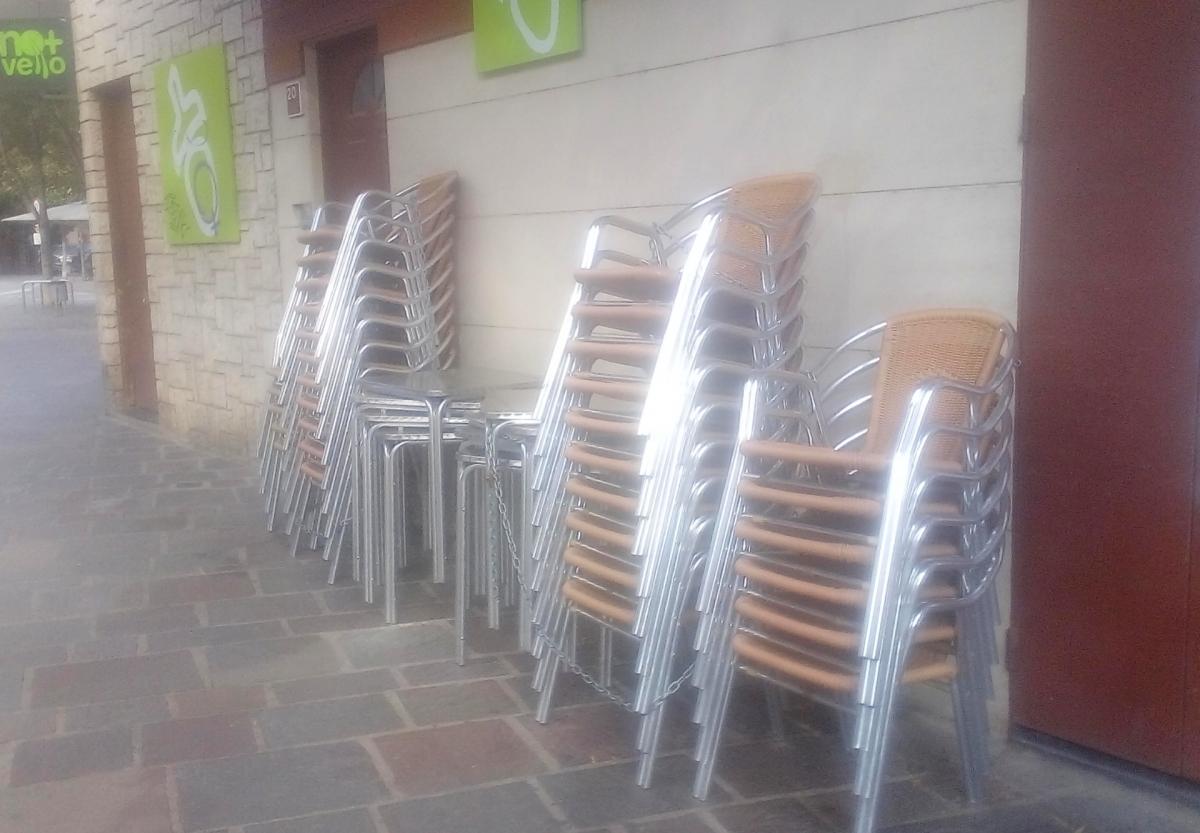El mobiliari d'una terrassa de la Plaça de la Creu, a punt d'obrir per les seves darreres hores abans del tancament