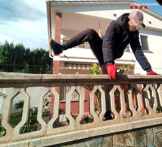 Un dels lladres del grup criminal saltant una tanca d'habitatge (Foto: Mossos)