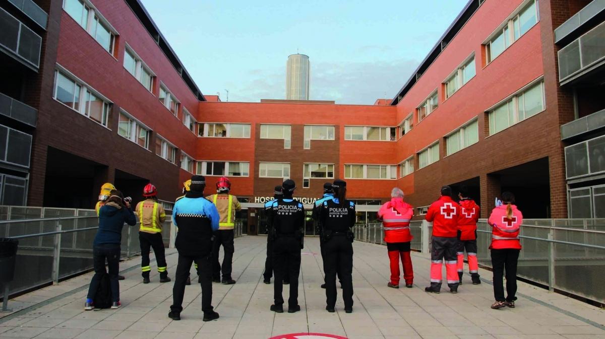 Bombers, policies i voluntaris de Creu Roja aplaudeixen els professionals de l'Hospital d'Igualada i donen ànims als pacients ingressats al centre. (Foto: Santi Vidal)