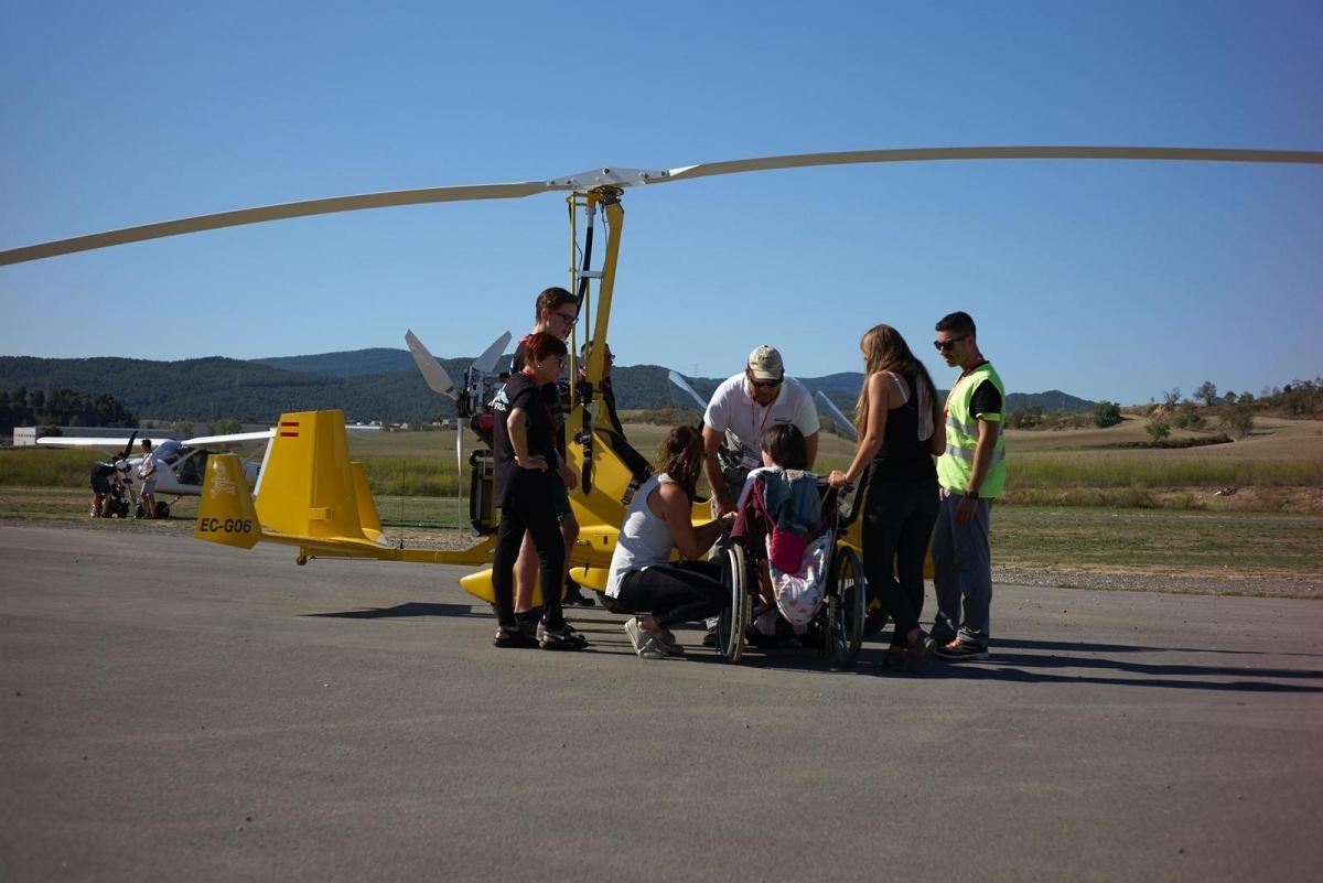 Un grup de voluntaris ajuda a una de les persones que s'estrenava en els vols