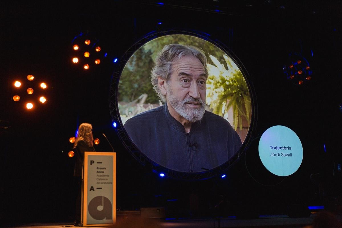 La imatge de Savall, a la pantalla situada a l'escenari del teatre