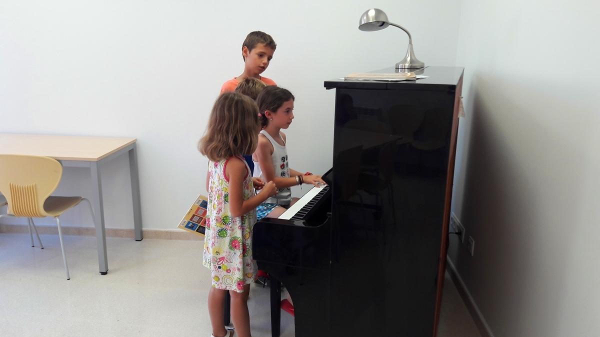 Tres dels alumnes, en una pràctica amb el piano