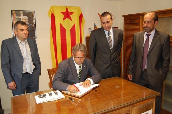Ernest Benach, acompanyat de Carles Pol i altres representants, signant en el llibre d'honor